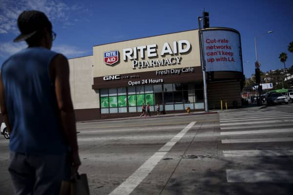 A pedestrian crosses the street in front of a Rite Aid Corp. store in Los Angeles, California.