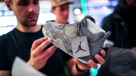 A KAWS x Air Jordan IV buyer looks at the shoe at a store on March 31, 2017 in Berlin, Germany.