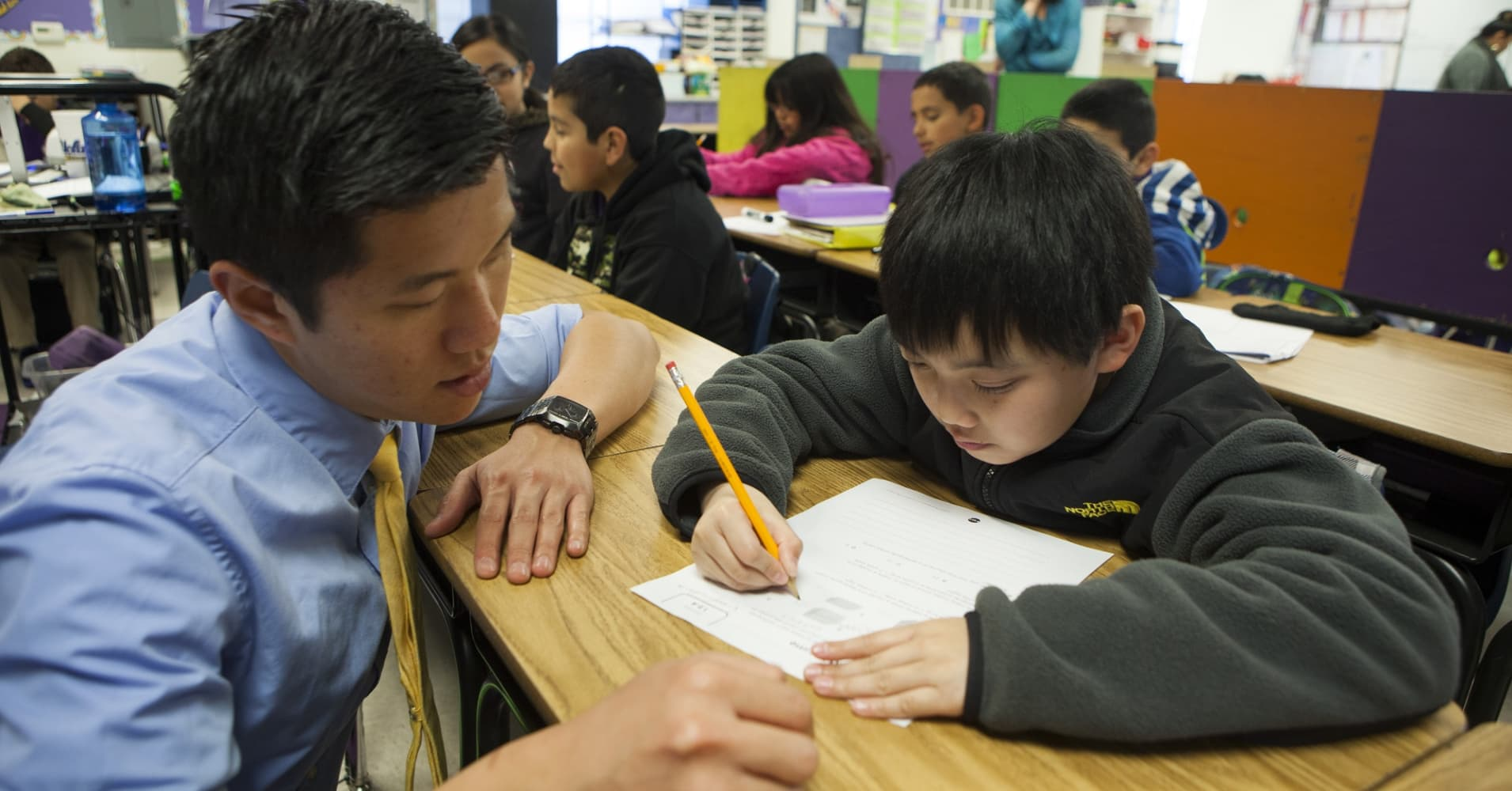 Fifth grade science and math teacher helps a student in San Jose, California.