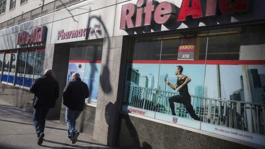 Pedestrians walk past a Rite Aid store in New York.