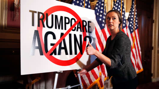 "A staffer places a sign that says ""Trumpcare Again?"" with a ""no"" symbol over it, before a news conference with Senate Minority Leader Sen. Chuck Schumer of N.Y., Monday, Sept. 18, 2017, on Capitol Hill in Washington."