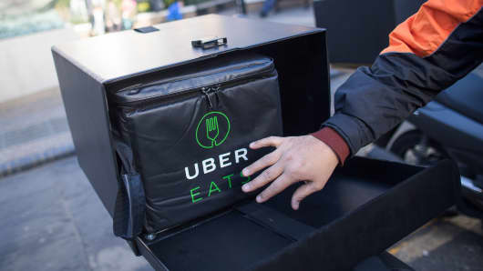 A food delivery courier puts an insulated food bag in his UberEats, operated by Uber Technologies Inc.