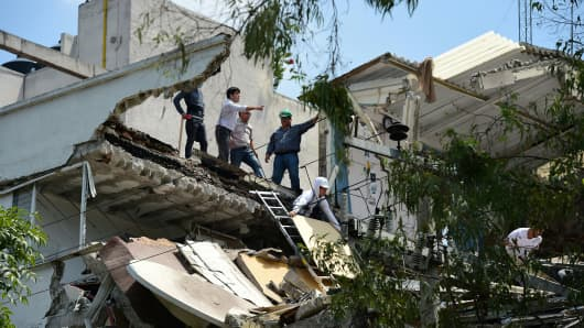 People remove debris of a damaged building after a real quake rattled Mexico City on September 19, 2017 while an earthquake drill was being held in the capital.