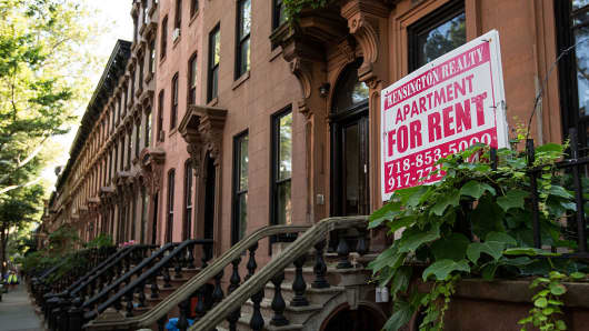 A sign advertises an apartment for rent along a row of brownstone townhouses in Brooklyn, New York.