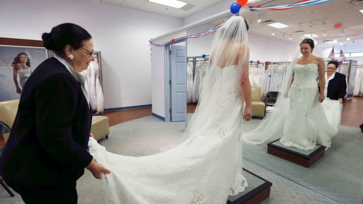 A customer tries on a wedding gown at Alfred Angelo Bridal, Nov. 11, 2015, in Cherry Hill, N.J.