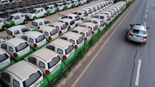 This photo taken on May 22, 2017 shows a car passing new electric vehicles parked in a parking lot under a viaduct in Wuhan, central China's Hubei province.