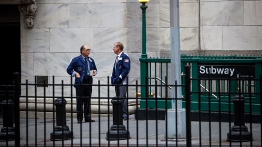 Traders stand outside of the New York Stock Exchange (NYSE) in New York.