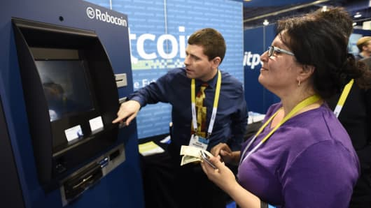 Nick Morphis of CoinVault ATM helps attendee Firouzeh Forouzmand (R) use the Robocoin ATM at the Bitcoin stand at the Consumer Electronics Show in Las Vegas, Nevada.