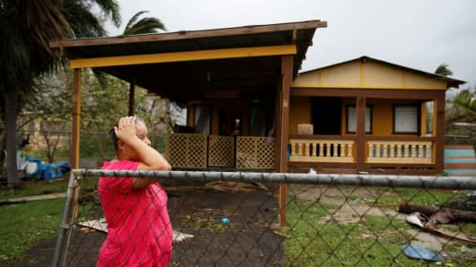 A woman reacts while looking at the damage to her house after the area was hit by Hurricane Maria in Guayama, Puerto Rico September 20, 2017.
