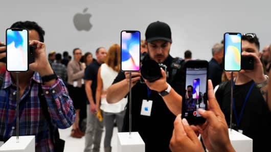 Attendees take pictures of new IPhone models during an Apple launch event in Cupertino, California, September 12, 2017.