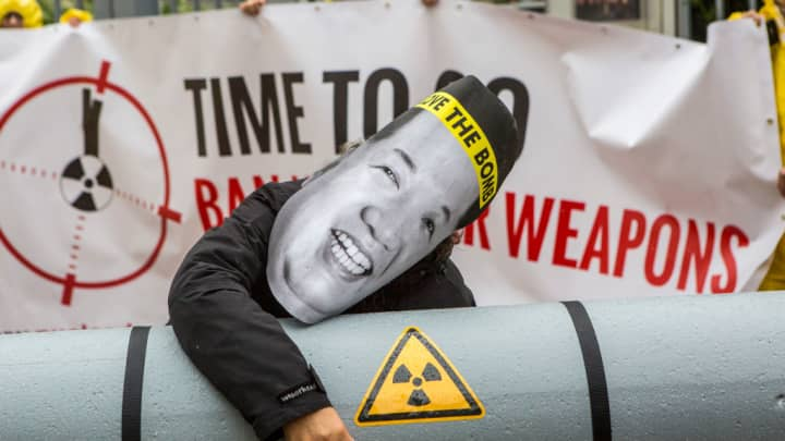 An activists wearing a mask with an image of North Korean leader Kim Jong-Un is posing next to a Styrofoam effigy of a nuclear bomb while protesting outside the North Korean Embassy on September 13, 2017 in Berlin, Germany.