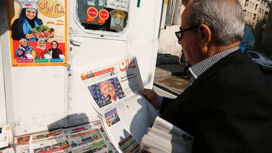 An Iranian man holds a local newspaper displaying a portrait of Donald Trump a day after his election as the new US president, in the capital Tehran, on November 10, 2016.