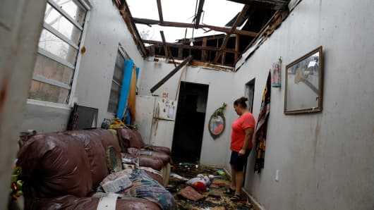 A woman looks at the damages in the neighbour's house after the area was hit by Hurricane Maria in Salinas, Puerto Rico, September 21, 2017.