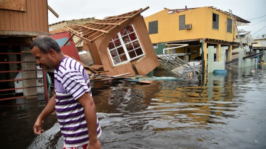 A man walks past a house laying in flood water in Catano town, in Juana Matos, Puerto Rico, on September 21, 2017.