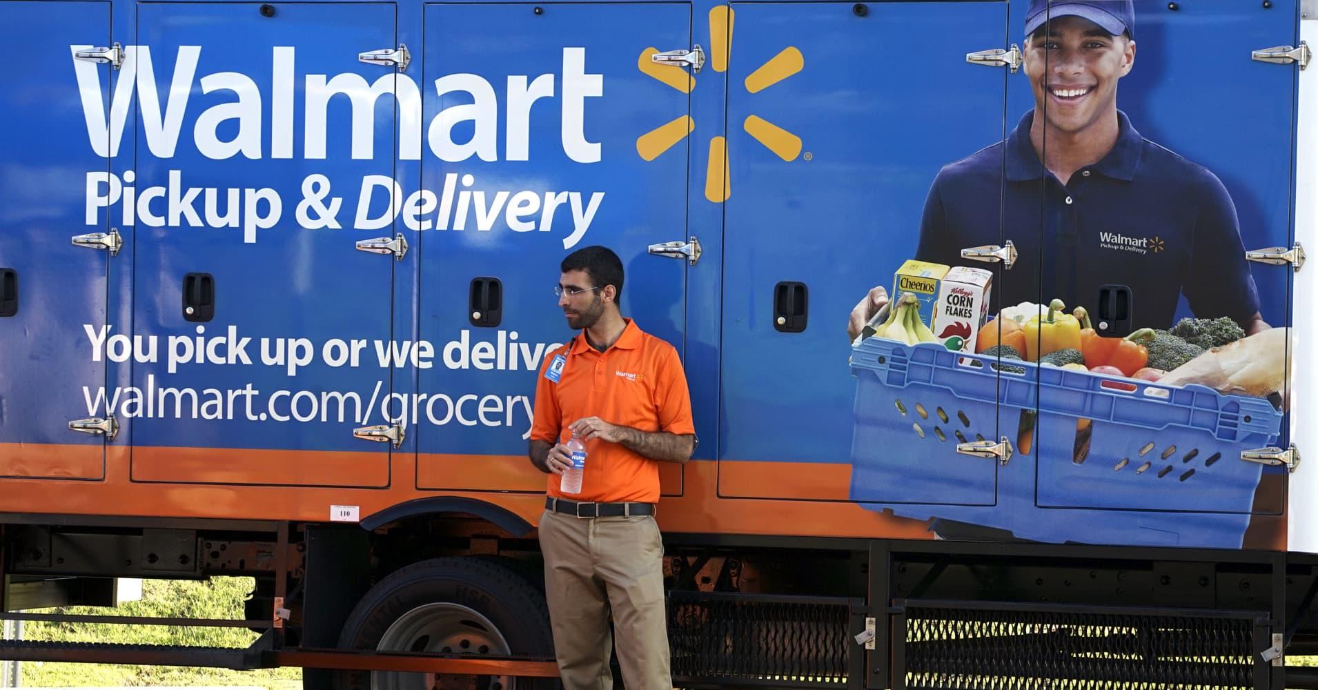 A Walmart Pickup-Grocery employee waits next to a truck.