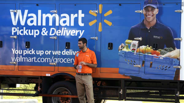 A Walmart Pickup-Grocery employee waits next to a truck.