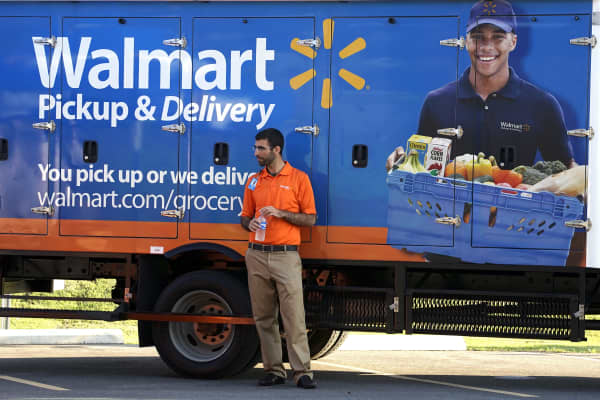 A Wal-Mart Pickup-Grocery employee waits next to a truck.