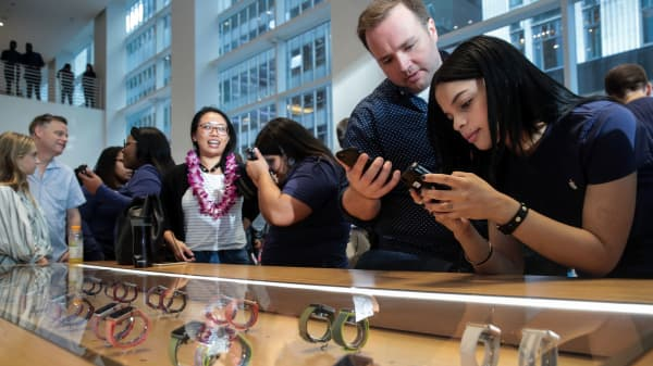 An Apple employee assists a customer with the new Apple iPhone 8 at the Fifth Avenue Apple Store, September 22, 2017 in New York City.