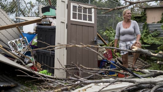 A resident surveys the damage on her property after Hurricane Maria made landfall, September 21, 2017 in the Guaynabo suburb of San Juan, Puerto Rico.