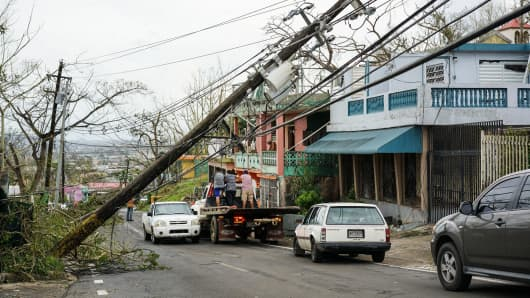 Motorists evade a power line post after Hurricane Maria near Santa Elena in Bayamón, Puerto Rico on September 21, 2017.