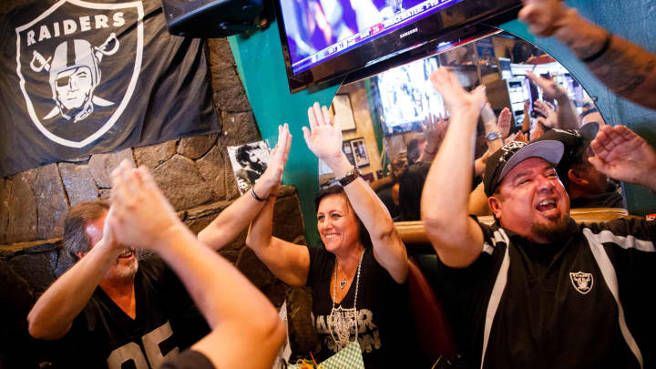 Raiders Fans watch an NFL football game between the Oakland Raiders and Baltimore Ravens in Huntington Beach, CA.