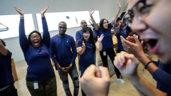 Apple employees cheer as the doors are opened for customers at the Fifth Avenue Apple Store, September 22, 2017 in New York City.