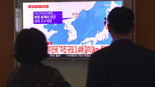 People watch a television news screen showing a map of the epicenter of an earthquake in North Korea, at a railway station in Seoul on September 23, 2017. China's seismic service CENC on September 23 detected a zero-depth, 3.4-magnitude earthquake in North Korea, calling it a 'suspected explosion'.