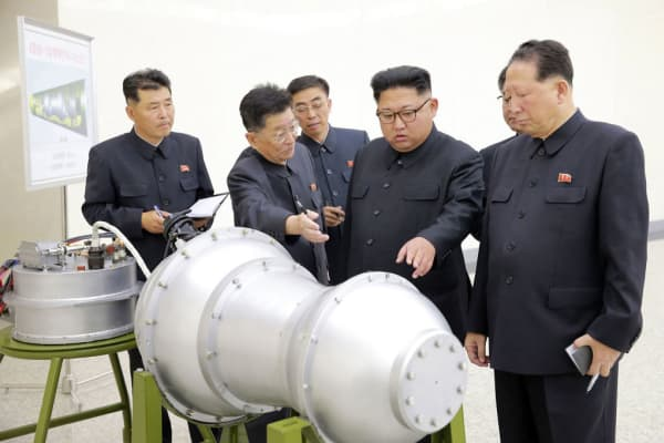 North Korean leader Kim Jong Un (C) looks at a metal casing at an undisclosed location an an undated picture released by North Korea's Korean Central News Agency.