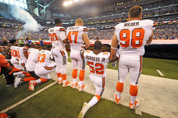 The Cleveland Browns team stand and kneel during the National Anthem before the start of their game against the Indianapolis Colts at Lucas Oil Stadium, September 24, 2017.
