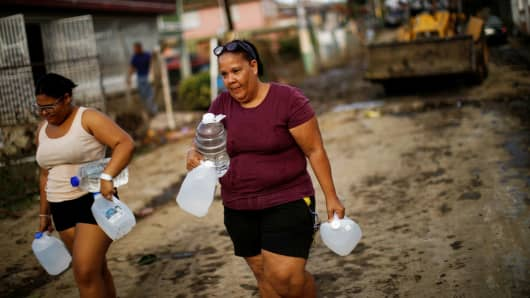 Women carry containers filled with water as workers use a backhoe loader to remove mud and debris from the street after the area was hit by Hurricane Maria in Toa Baja, Puerto Rico September 24, 2017.