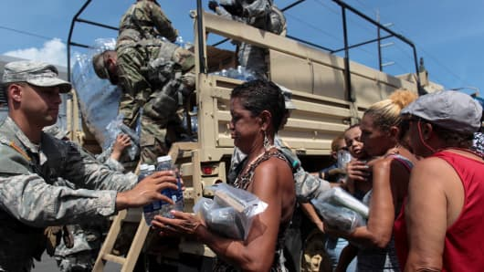 Soldiers of Puerto Rico's national guard distribute relief items to people, after the area was hit by Hurricane Maria in San Juan, Puerto Rico September 24, 2017.