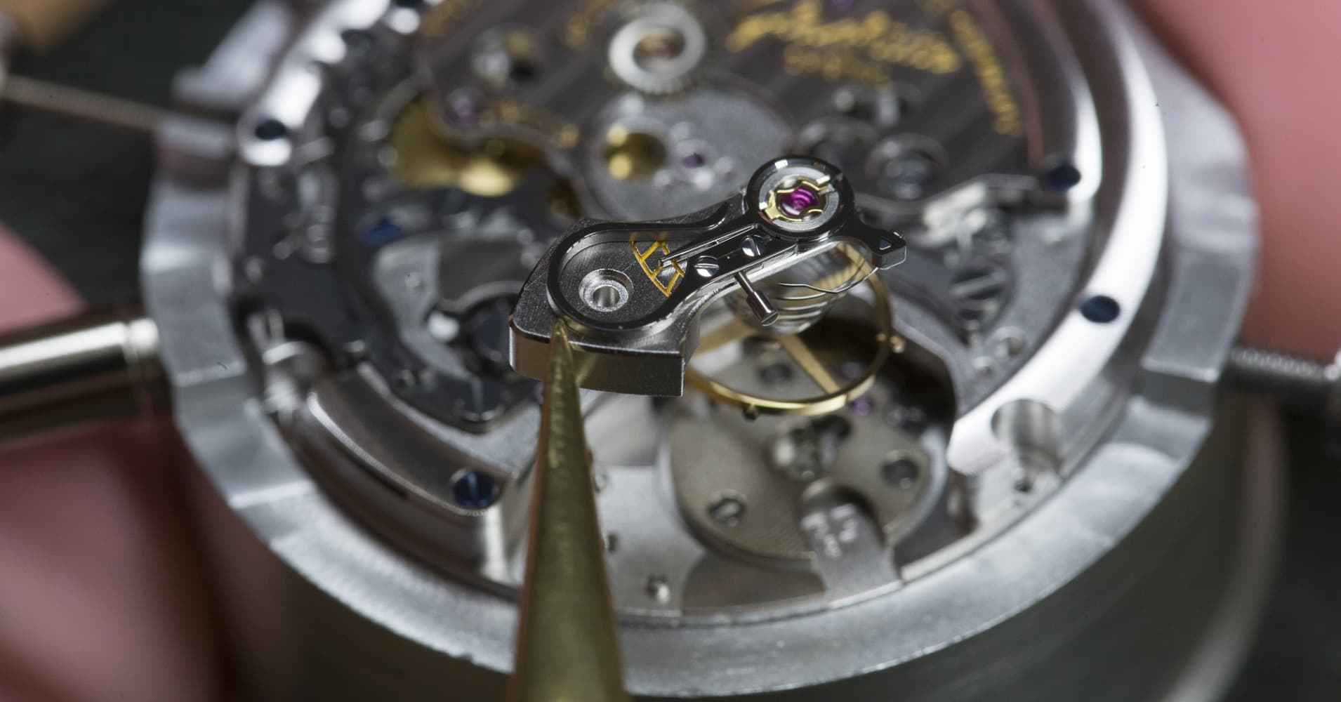 A watchmaker prepares to position an escapement wheel during the assembly of a Senator Chronograph Panorama Date luxury wristwatch at the Glashuette Original watch factory.