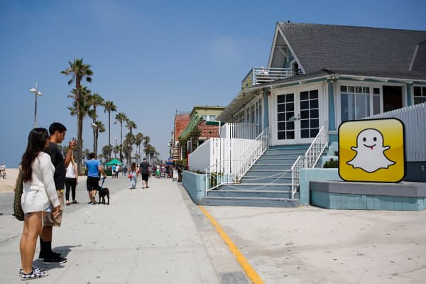 People take pictures in front of the Snap headquarters on the strand at Venice Beach in Los Angeles.