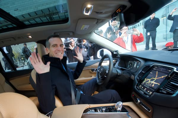 Mayor of Los Angeles Eric Garcetti as he sits, hands in the air, behind the wheel in a self-driving, autonomous car at a car show in California.