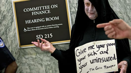 A man dressed as the grim reaper, who is opposed to the Graham-Cassidy-Heller-Johnson proposal, stands outside the Senate Finance Committee hearing room ahead of a hearing in Washington, D.C., U.S., on Monday, Sept. 25, 2017.