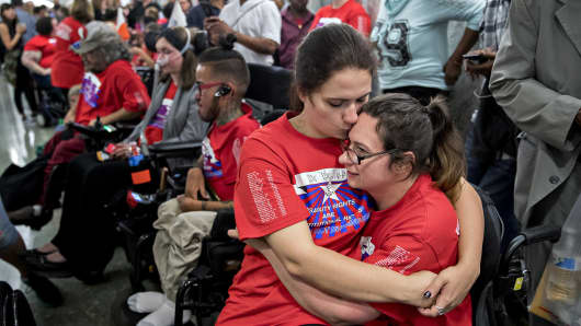 Sisters Shaylin Sluzalis, left, and Brittani Sluzalis, members of the disability rights group ADAPT, embrace while waiting in line before a Senate Finance Committee hearing to consider the Graham-Cassidy-Heller-Johnson proposal in Washington, D.C., U.S., on Monday, Sept. 25, 2017.