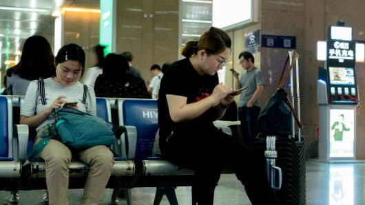 People read on mobile phone while waiting for the train in Tianjin railway station.