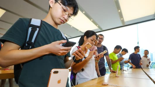Customers try iPhones at the Apple store in Hong Kong, China.