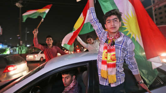 Iraqi Kurds wave the Kurdish flag as they celebrate in the streets of the northern city of Arbil on September 25, 2017 following a referendum on independence.