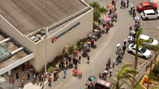 A line of people wraps around the Banco Popular in San Juan as people are desperate to get cash. Nearly one week after hurricane Maria devastated the island of Puerto Rico, residents are still trying to get the basics of food, water, gas, and money from banks.