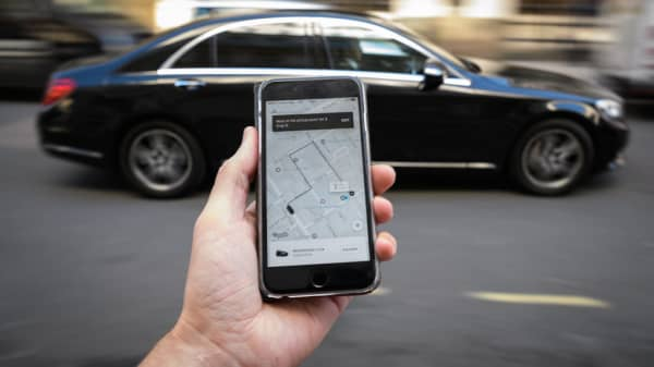 A phone displays the Uber ride-hailing app on September 22, 2017 in London, England.