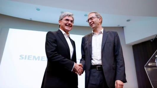 German ICE train manufacturing company Siemens President and CEO, Joe Kaeser (L) shakes hands with French railway transport company Alstom CEO, Henri Poupart-Lafarge following a press conference announcing the union between French railway transport company Alstom and Siemens on September 27, 2017 in Paris.