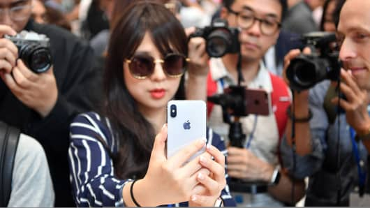 People take photos as a woman tests out a new iPhone X during a media event at Apple's new headquarters in Cupertino, California on September 12, 2017.