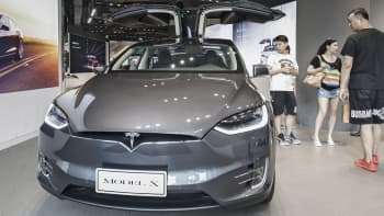 Customers look at a Tesla Motors Inc. Model X electric vehicle on display at the company's showroom in Shanghai, China, on Tuesday, Sept. 12, 2017.