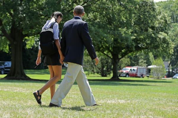 President Barack Obama and his daughter Malia Obama walk hand-in-hand.