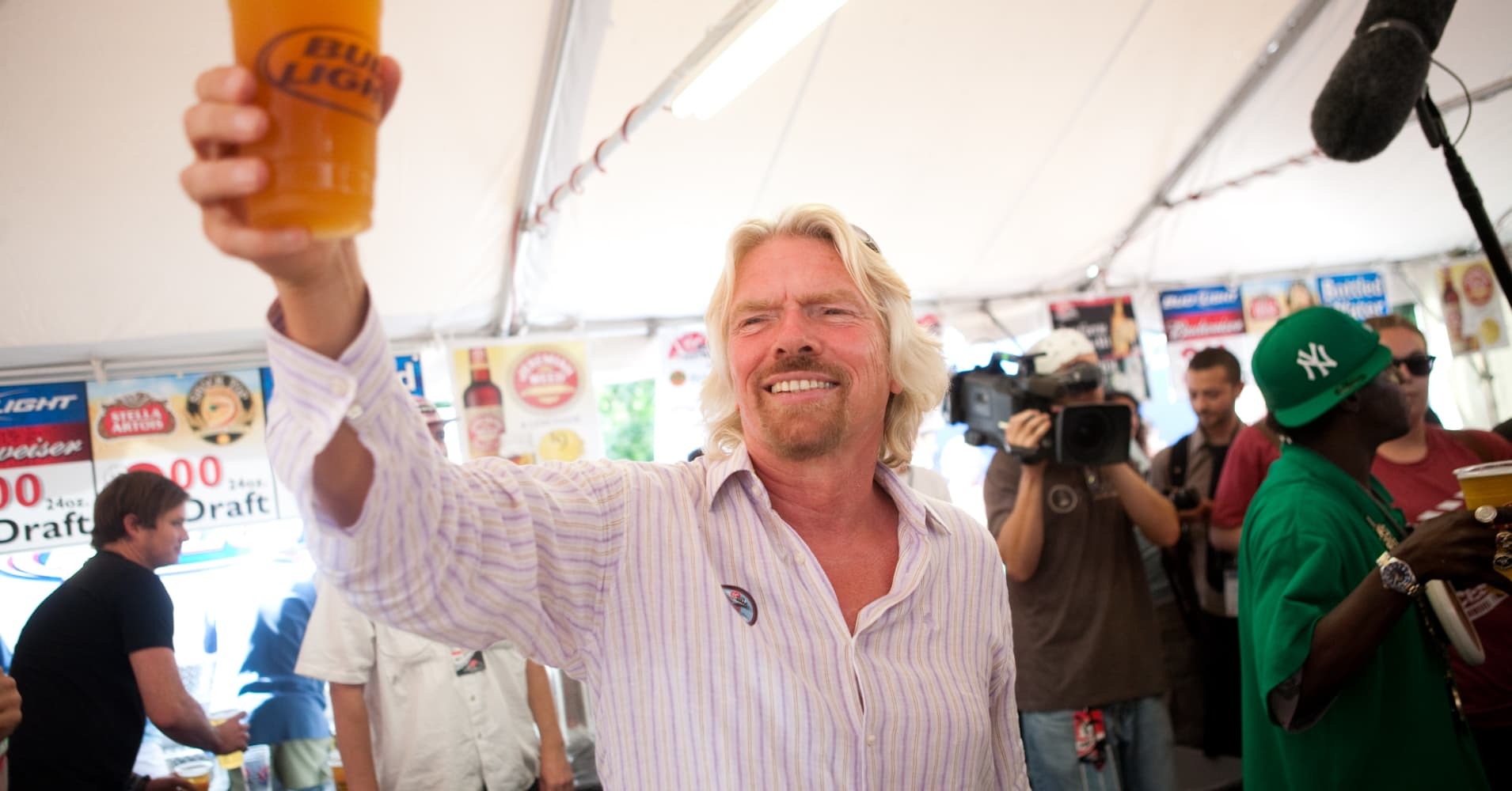 Sir Richard Branson serves beer at the Virgin Mobile FreeFest in 2009.