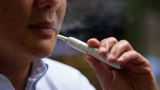 A man smokes a Philip Morris International iQOS electronic cigarette in this arranged photograph in Tokyo.