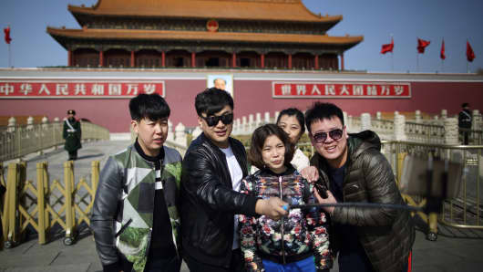 People take a 'selfie' photograph with a handheld monopod in front of Tiananmen Gate in Beijing, China.
