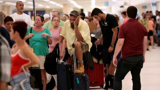 Stranded tourists and Puerto Ricans line up at the International Airport as they try to leave after Hurricane Maria devastated power and communications across the island, in San Juan, Puerto Rico September 25, 2017.
