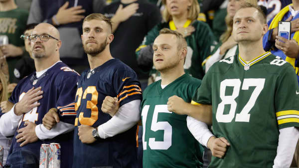 Fans lock arms during the national anthem before an NFL football game between the Green Bay Packers and the Chicago Bears Thursday, Sept. 28, 2017, in Green Bay, Wis.